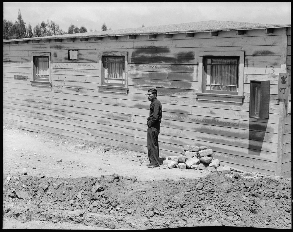 June 16, 1942 — San Bruno, California. Many evacuees suffer from lack of their accustomed activity. The attitude of the man shown in this photograph is typical of the residents in assembly centers, and because there is not much to do and not enough work available, they mill around, they visit, they stroll and they linger to while away the hours.
