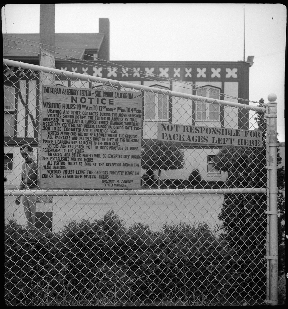 June 16, 1942 — San Bruno, California. A sign at the main entrance of the Tanforan Assembly center, through which all traffic passes. The gate is guarded and controlled by United States soldiers.