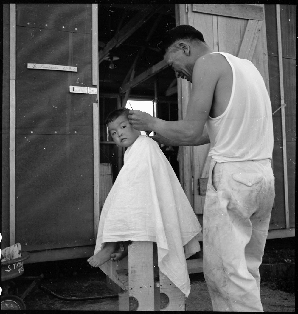 PRINT AVAILABLE   July 2, 1942 — Manzanar Relocation Center, Manzanar, California. Little evacuee of Japanese ancestry gets a haircut.