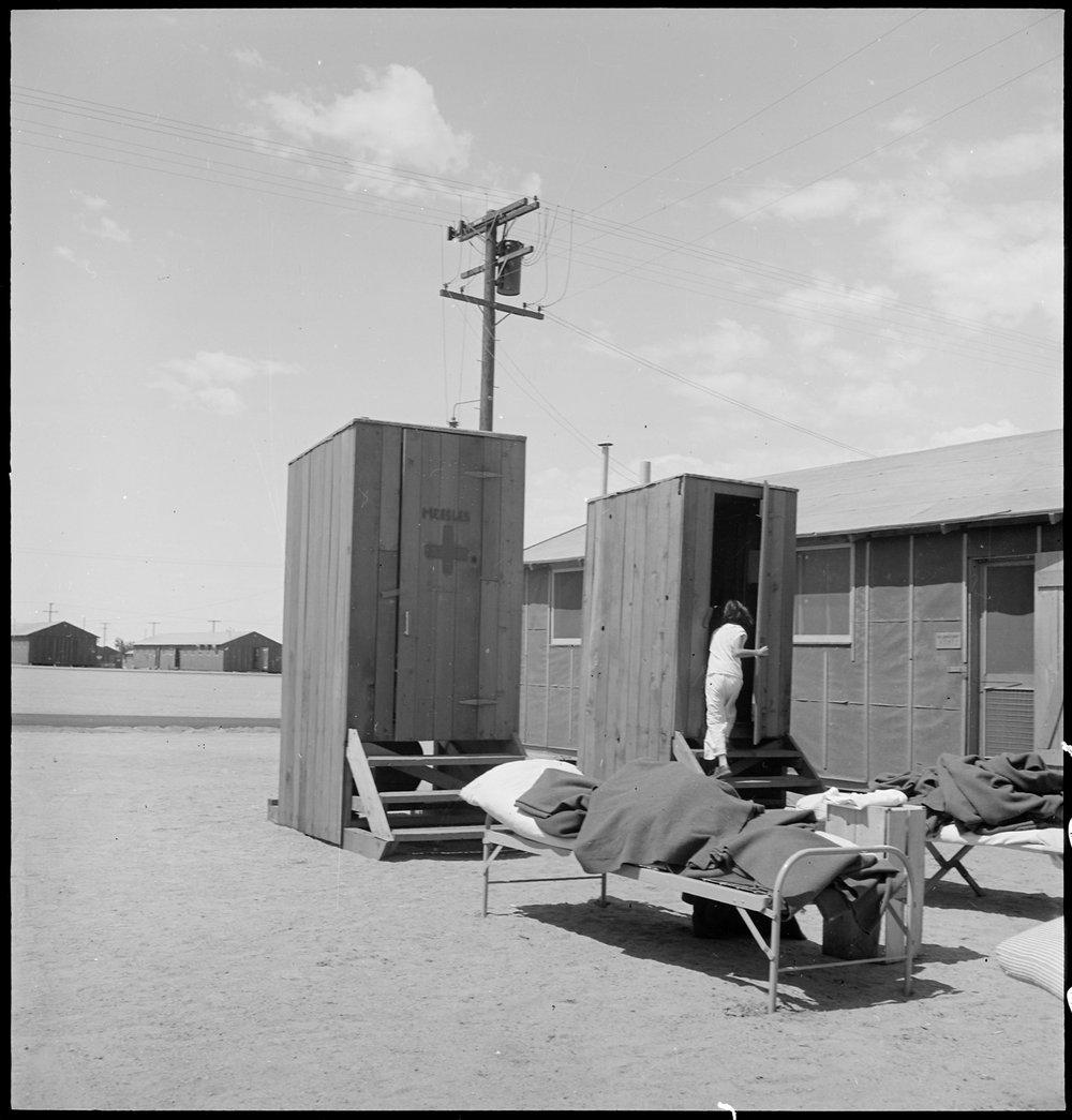 Manzanar Relocation Center, Manzanar, California. Hospital latrines, for patients, between the barr . . .