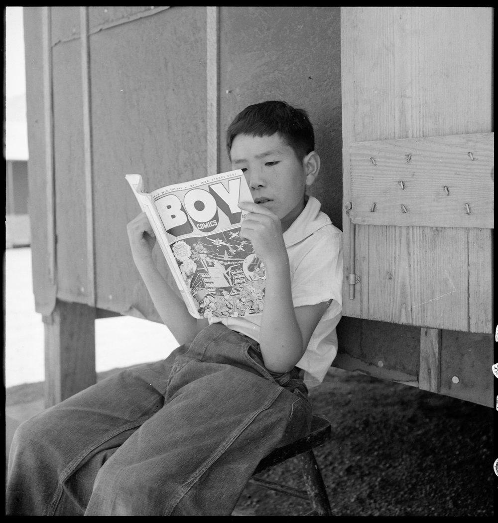 Manzanar Relocation Center, Manzanar, California. Evacuee boy at this War Relocation Authority center reading the Funnies.