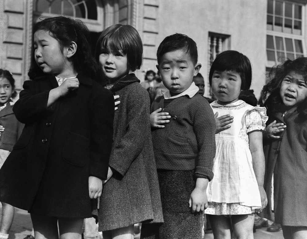 PRINT AVAILABLE   April 20, 1942 — San Francisco, California. Many children of Japanese ancestry attended Raphael Weill public School, Geary and Buchanan Streets, prior to evacuation. This scene shows first- graders during flag pledge ceremony. Evacuees of Japanese ancestry will be housed in War Relocation Authority centers for the duration. Provision will be effected for the continuance of education.