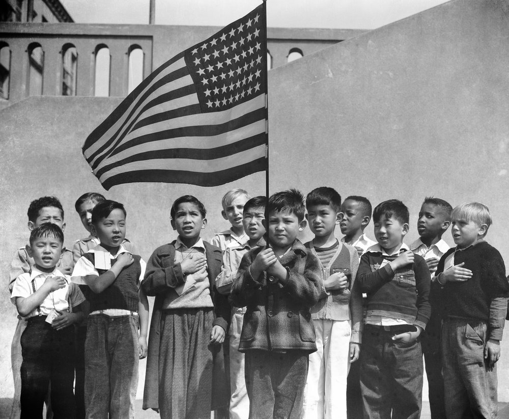 PRINT AVAILABLE   April 20, 1942 — San Francisco, California. Flag of allegiance pledge at Raphael Weill Public School, Geary and Buchanan Streets. Children in families of Japanese ancestry were evacuated with their parents and will be housed for the duration in War Relocation Authority centers where facilities will be provided for them to continue their education.