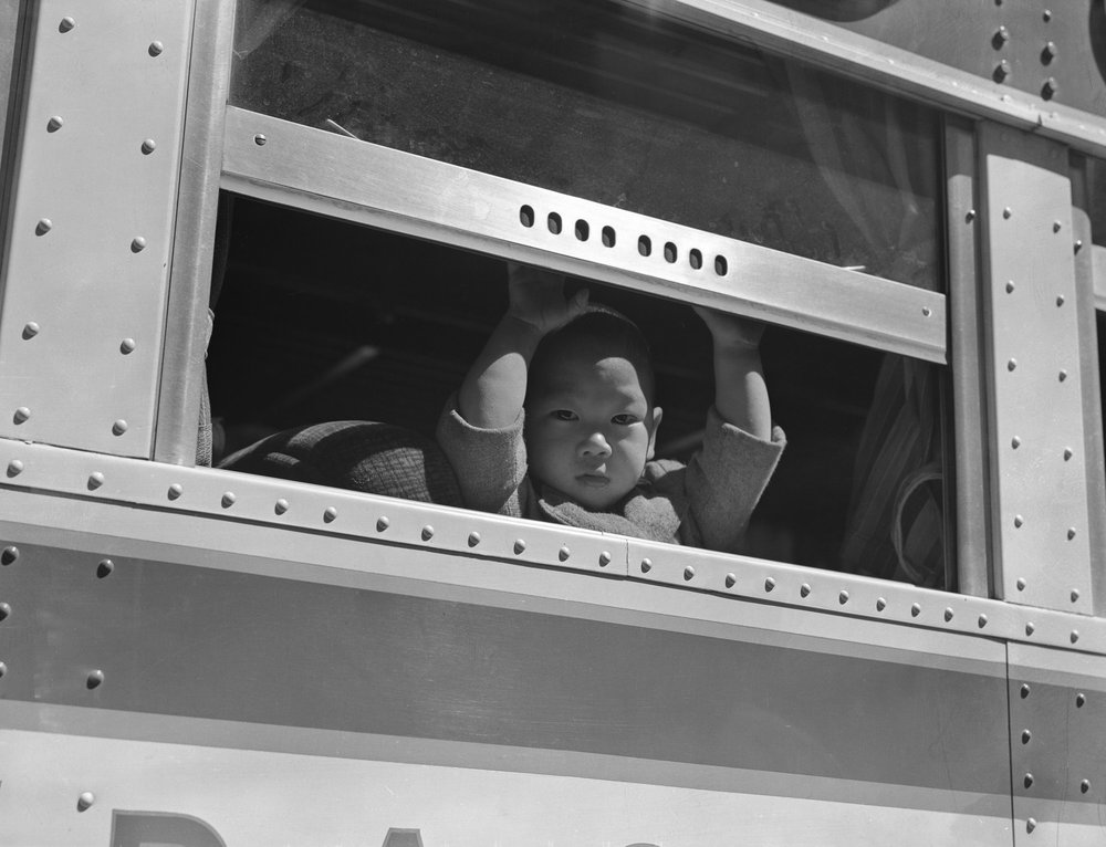 PRINT AVAILABLE   April 29, 1942 — San Francisco, California. A young evacuee looks out the window of bus before it starts for Tanforan Assembly center. Evacuees will be transferred to War Relocation Authority centers for the duration.