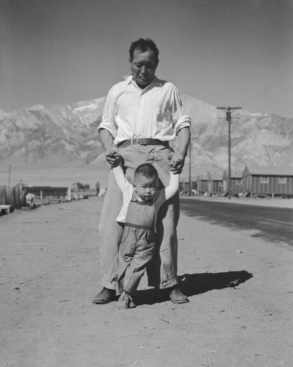 PRINT AVAILABLE   July 2, 1942 — Manzanar Relocation Center, Manzanar, California. Grandfather of Japanese ancestry teaching his little grandson to walk at this War Relocation Authority center for evacuees.