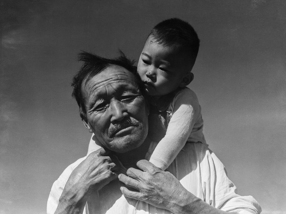 PRINT AVAILABLE   July 2, 1942 — Manzanar Relocation Center, Manzanar, California. Grandfather and grandson of Japanese ancestry at this War Relocation Authority center.