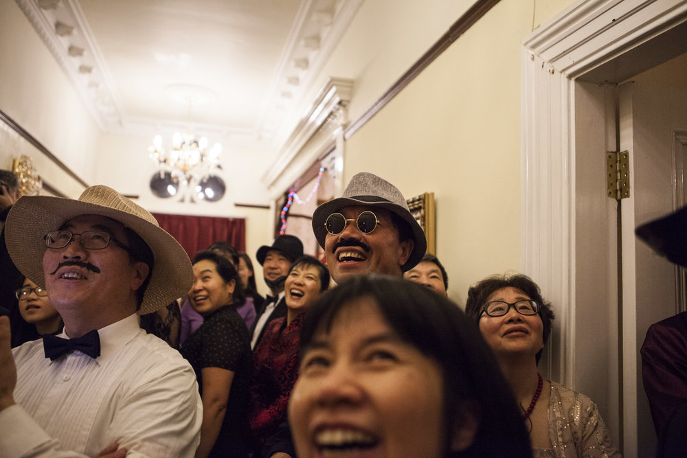 Crowd of Chinese parents watch in fancy dress as their friends perform a procession down the staircase.