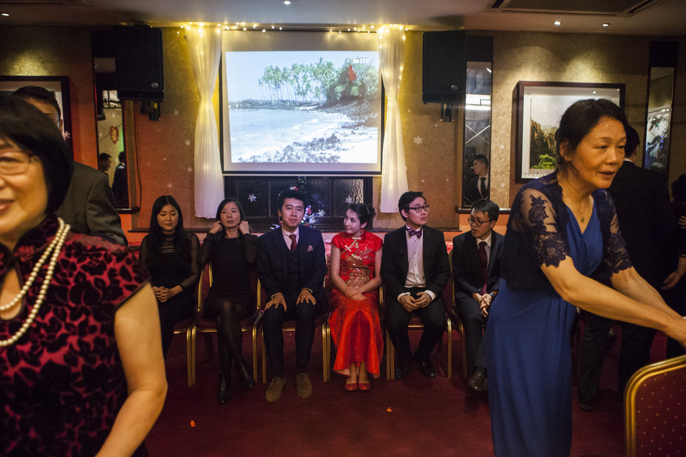 Second generation Chinese migrants sit with the bride and groom on stage while the parents prepare the venue for the next event.
