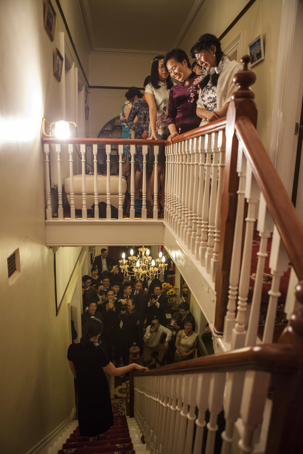 "Upstairs, the women line up in their traditional qi pao while the men wait downstairs to see the procession. As their wives descend, the crowd shouts, ""Whose younger sister is this?"" and take photographs as the women pose."