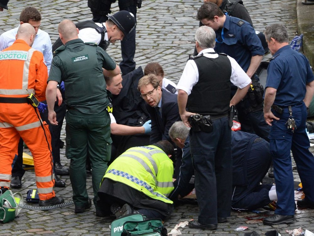 Conservative MP Tobias Ellwood (centre) helps emergency services attend to a police officer outside the Palace of Westminster PA