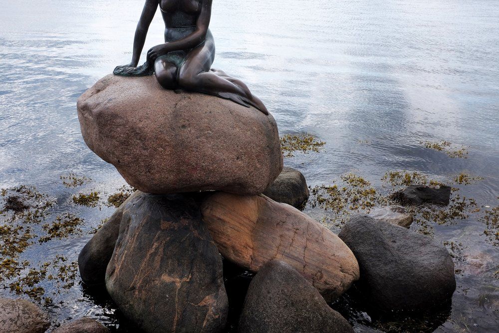 A statue of The Little Mermaid sits gracefully on the docks of Copenhagen as an homage to Danish author Hans Christian Andersen.
