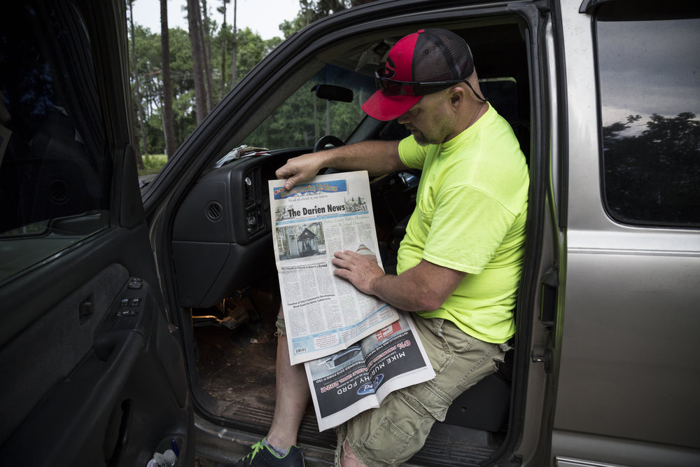 Patrick Young, the church's current caretaker, holds a newspaper article reporting on a fire at the church.