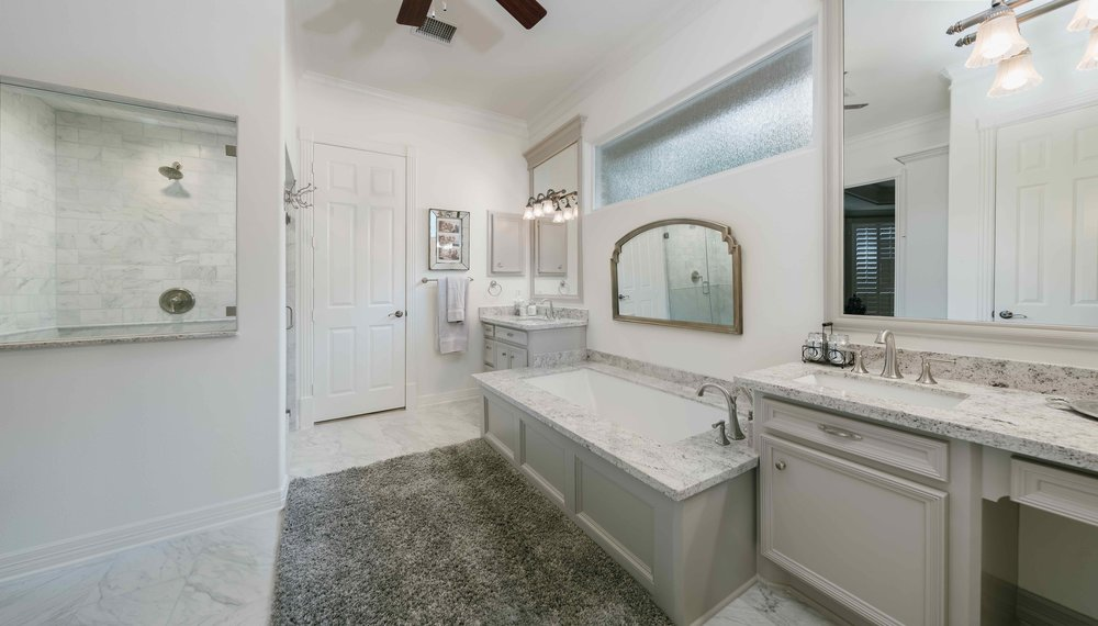 Tranquil master bathroom. Elegant tub, grey granite countertops, brushed nickel sinks, and luxurious rug.