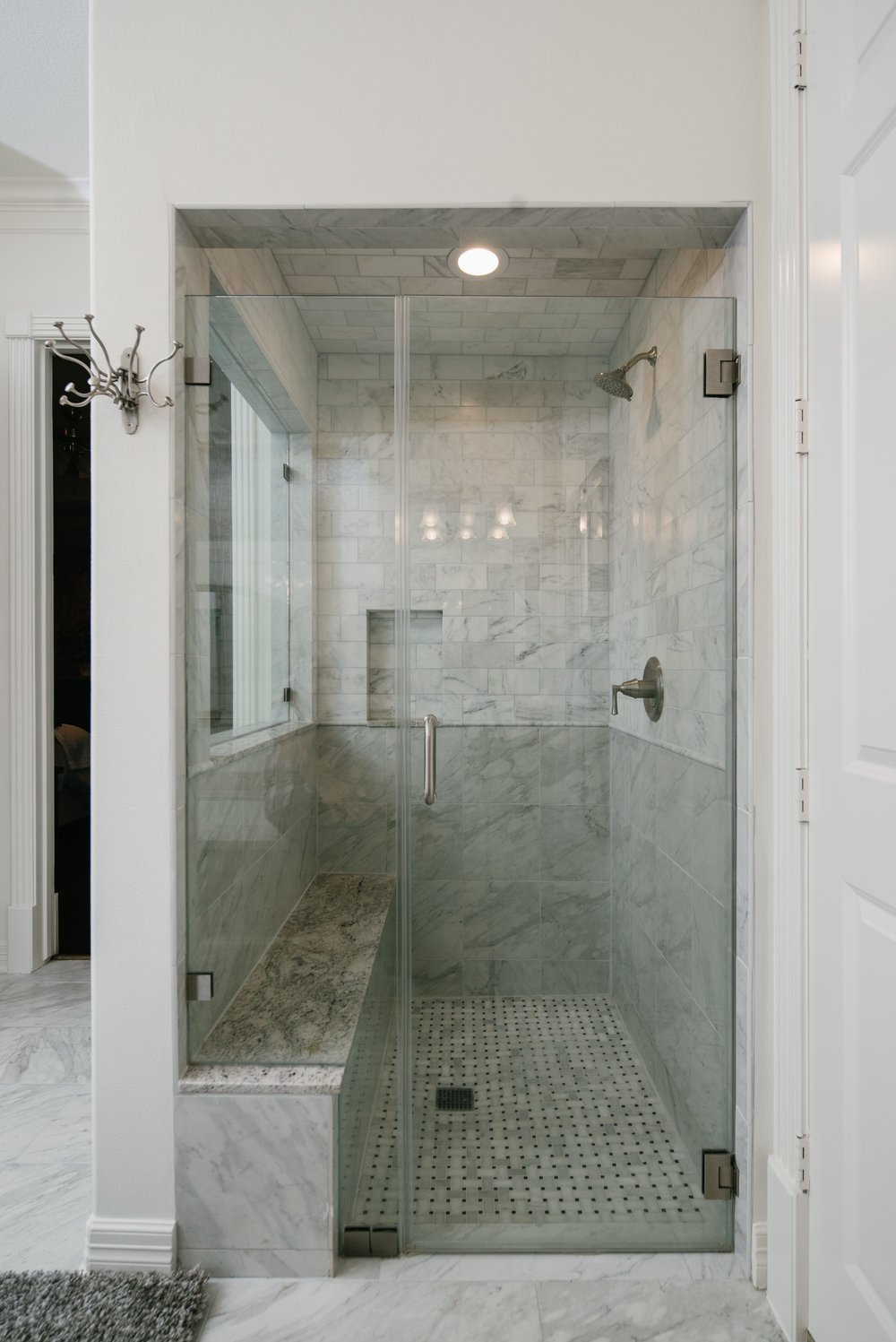Walk in shower a bench seat, shampoo niche, and frameless glass all completed with elegant grey tile.