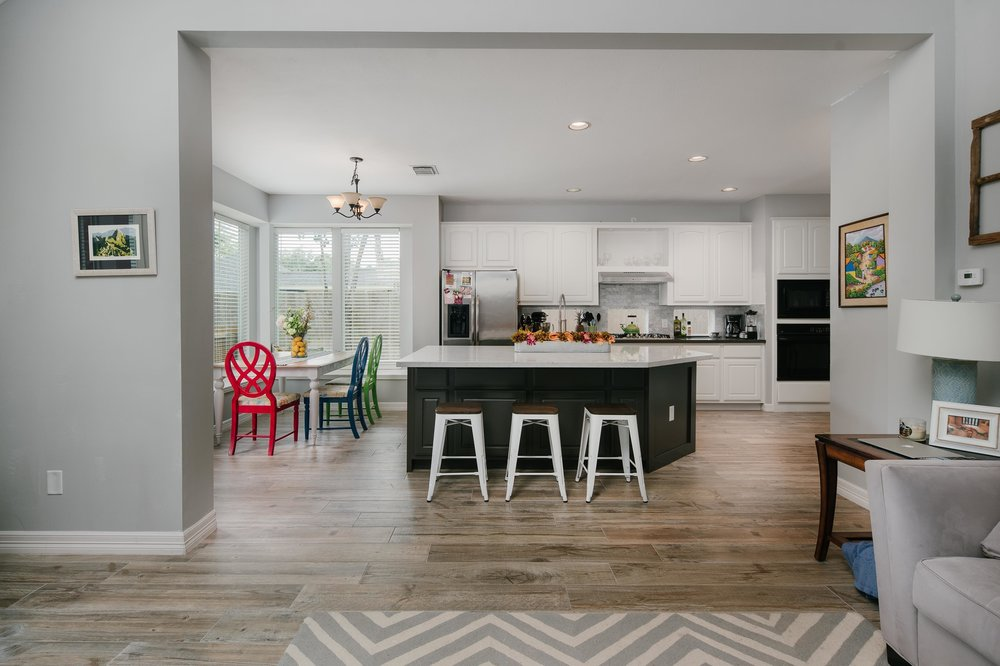 Warm family kitchen with an extended custom island topped with white quartz and finished off with custom paint. With weathered oak wood floor tile, two toned cabinets, black quartz countertops and a grey marble backsplash this kitchen is elegance with ease.
