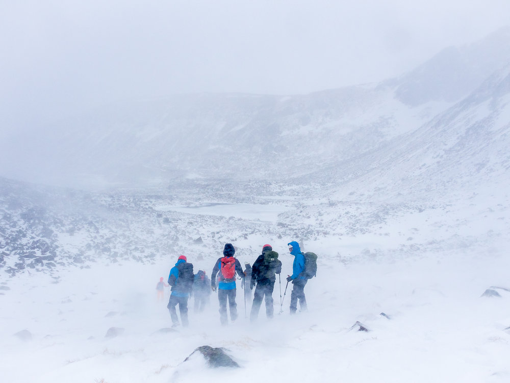 The team descends from cutting snow steps on the slopes of Corie an Sneachda during a blizzard.