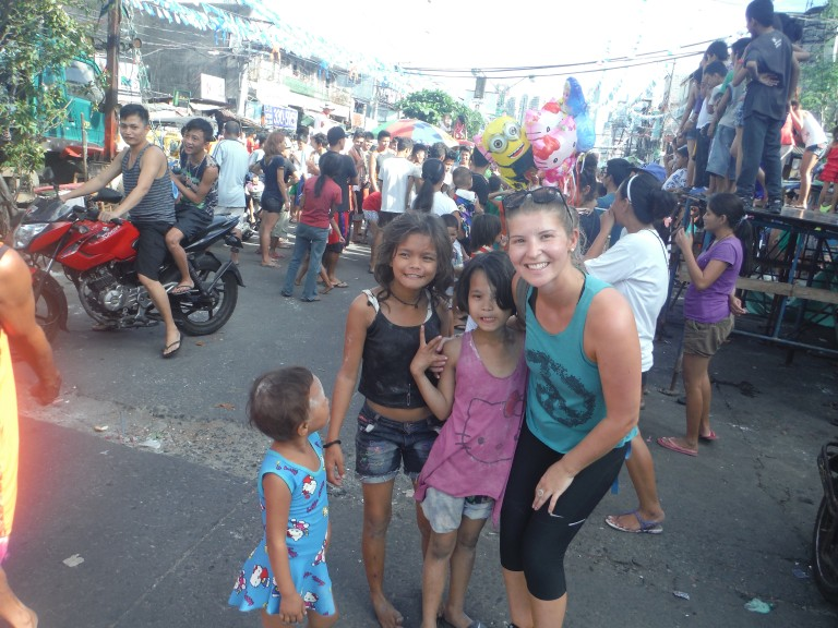 "The Wandering Quinn with some children on the ""True Manila"" tour"