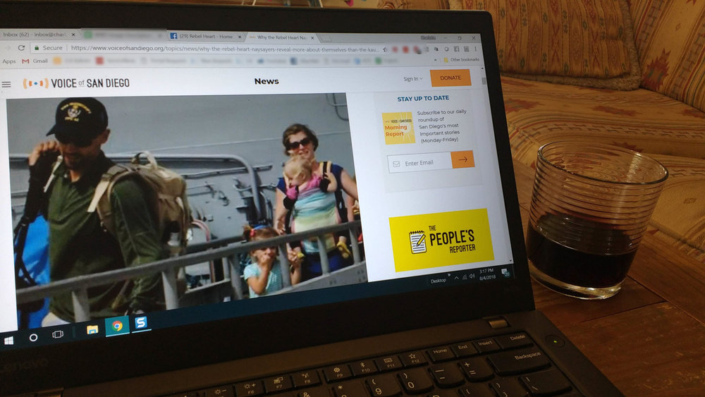 Image description: an open laptop with an article from the Voice of San Diego showing an article from April 2014 with a picture of Eric & Charlotte Kaufman and their two daughters debarking the USS Vandegrift. The laptop sits on a wooden table and a short glass of red wine to its right.