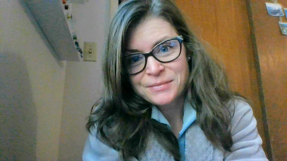 Image Description: Charlotte Kaufman wearing a pair of glasses and staring at the computer screen with slight smile on her face.