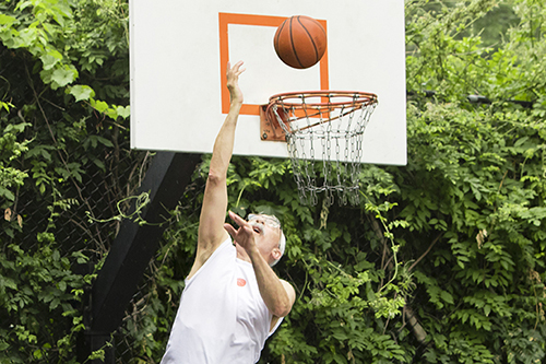 Basketball player dunks while wearing super lightweight UnderCool cooling vest.