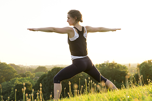 Woman practices yoga while wearing ultra-comfortable UnderCool cooling vest.