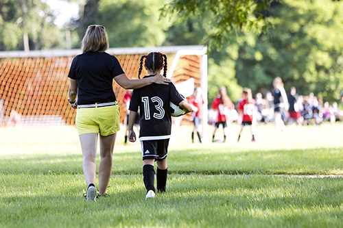 Mom wears invisible UnderCool cooling vest while at her daughter's soccer game.