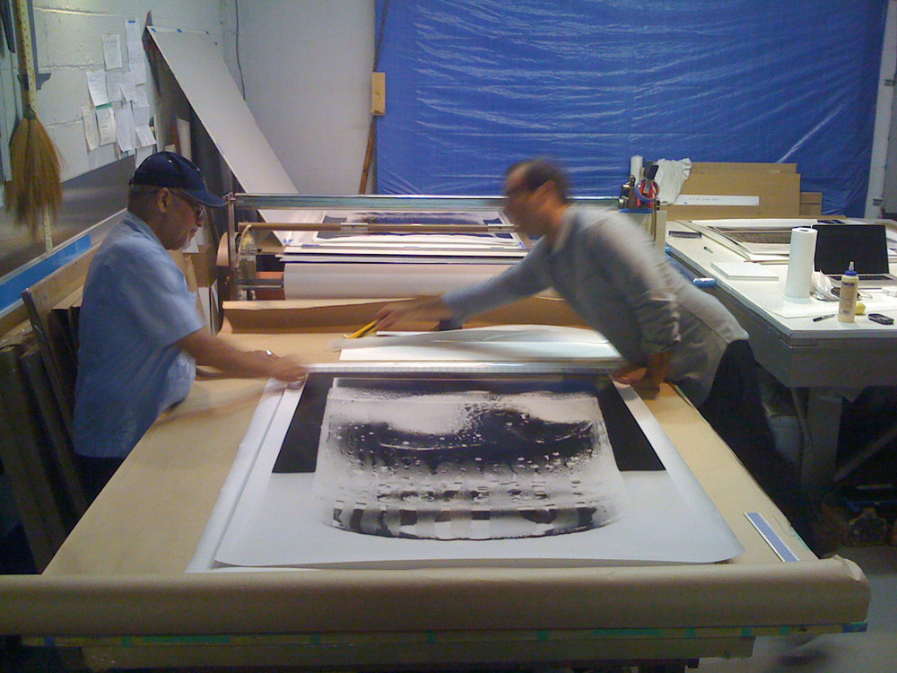 "Sam Merians and Joseph Rodriguez of Big Prints NYC mounting 50"" x 40"" prints."