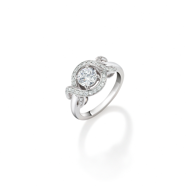 Diamond Love Bow Ring. Brilliant cut diamond entwined in a bow of channel set diamonds in platinum.