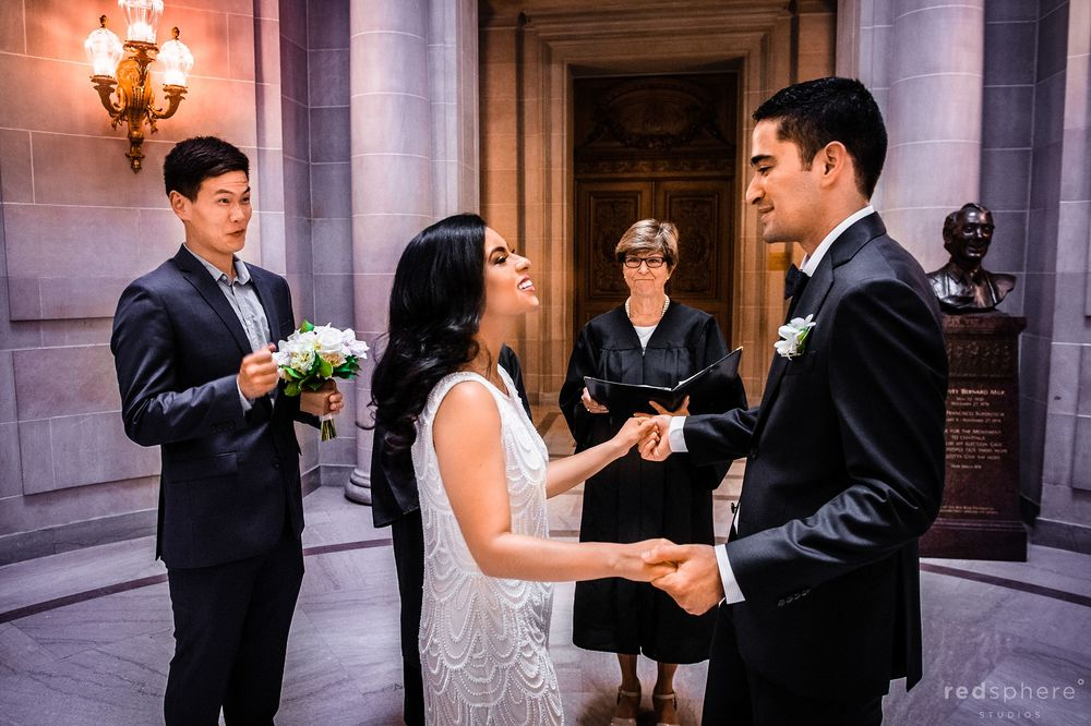 Bride and Groom Hold Hands during San Francisco City Hall Wedding Ceremony