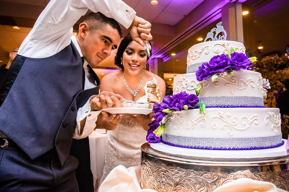 Groom Slicing Purple Flower Wedding Cake