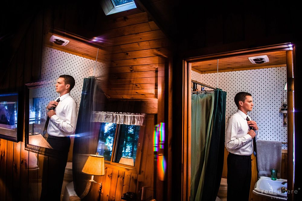 Groom Adjusting his tie in the Bathroom
