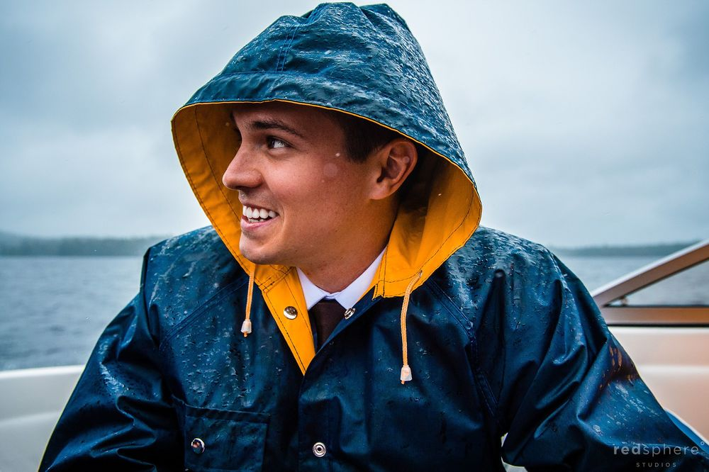 Groom Smiling on Rainy Boat Ride at Saranac Lake New York During Wedding day