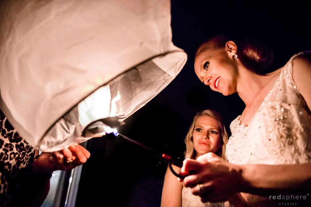 Bride Lighting Lanterns at Saranac Lake Wedding Reception