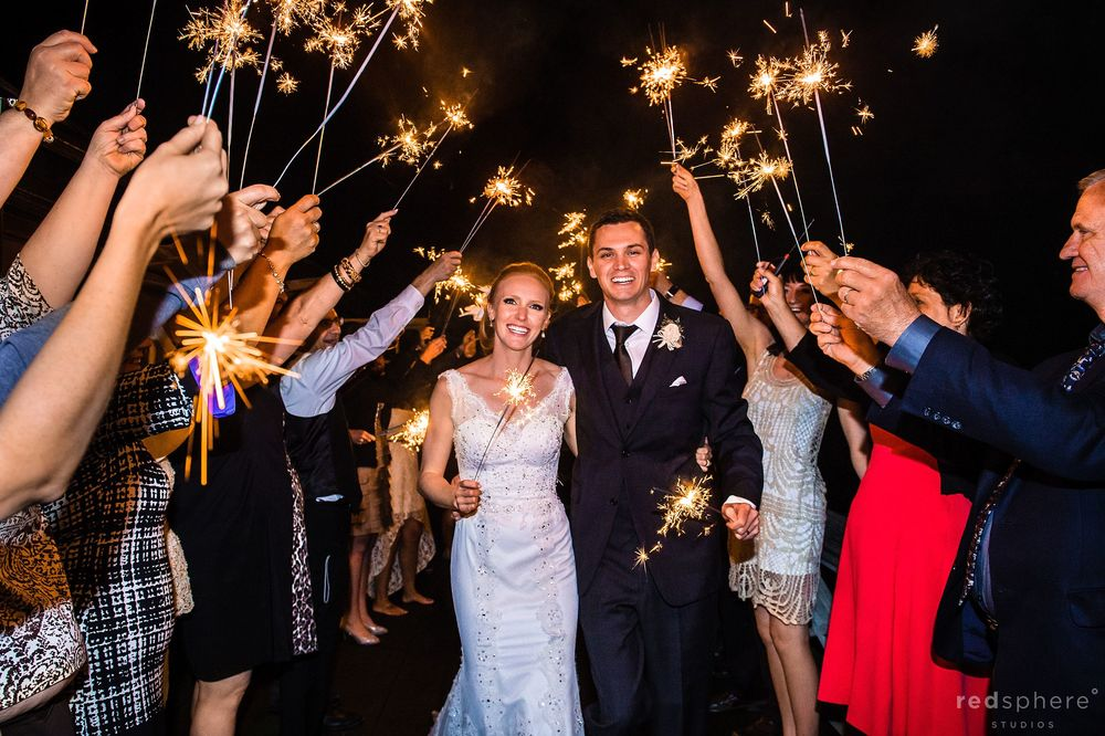 Bride and Groom Walk Together Surrounds by Guests With Sparklers