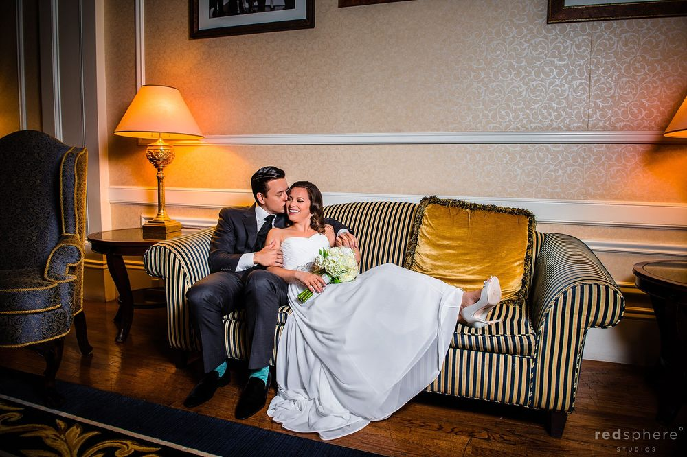 Bride and Groom Cuddling on a Love Seat Couch