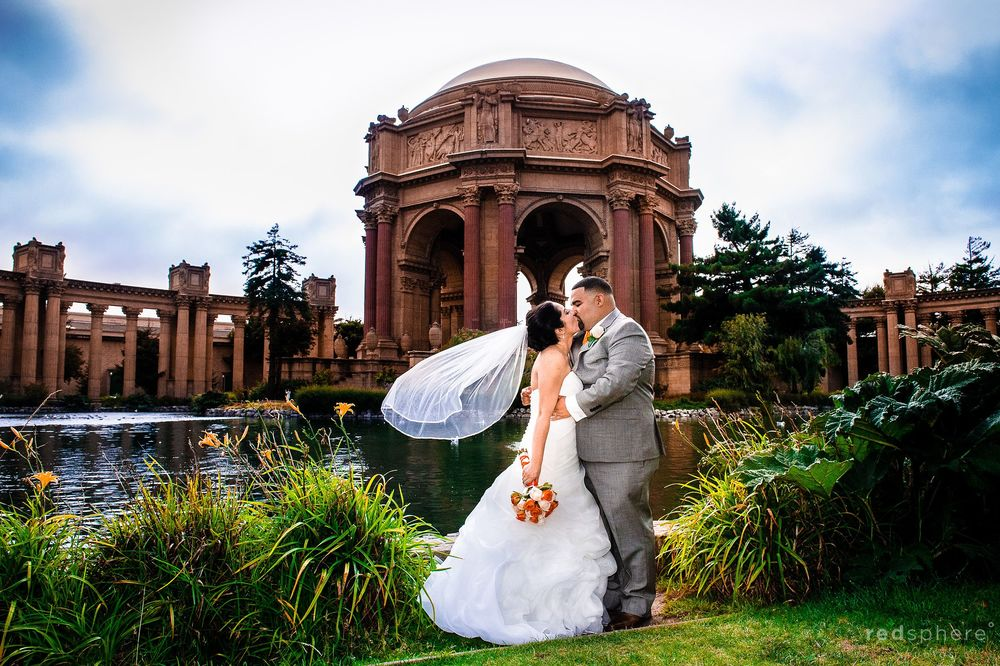 Bride and Groom Kiss on Green Grass at Palace of Fine Arts, Sunny San Francisco Days