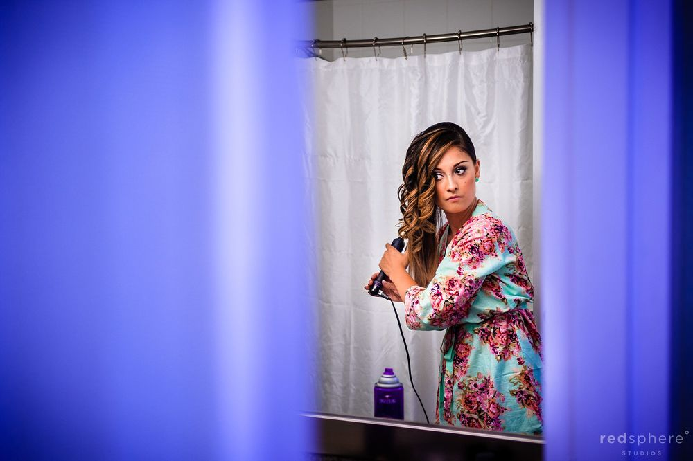 Bridesmaid Curling her Hair in the Bathroom as she Prepares for Wedding
