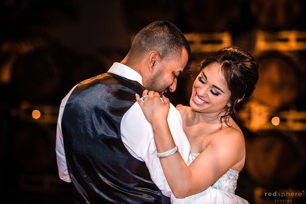 Bride Chuckles While Slow Dancing With Husband at Palm Event Center Pleasanton