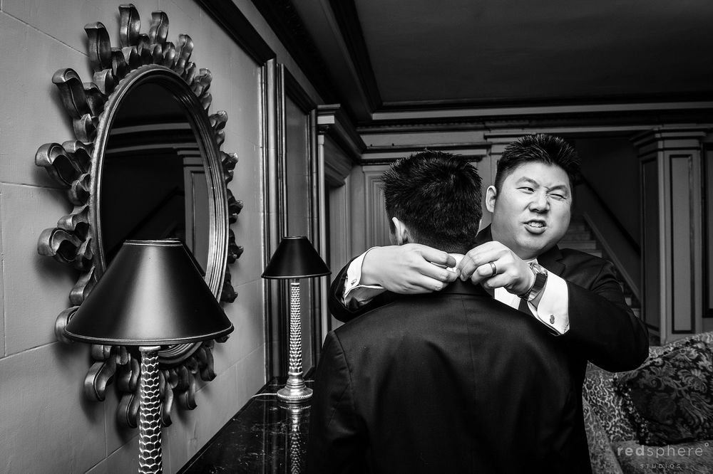 Groom Getting Help With Bow by Close Friend