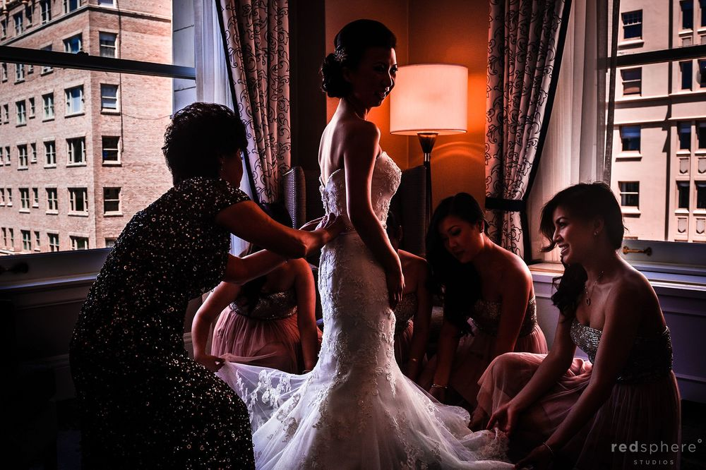 Bride Changing Into Wedding Dress With the Help of Bridesmaids