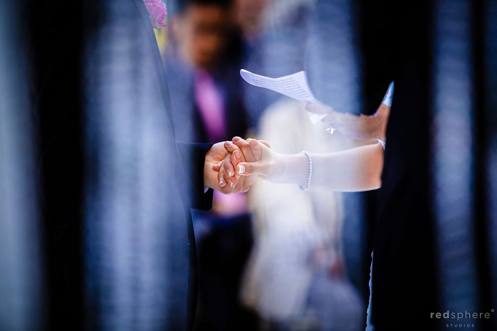 Bride and Groom Hold Hands as Vows are Being Said