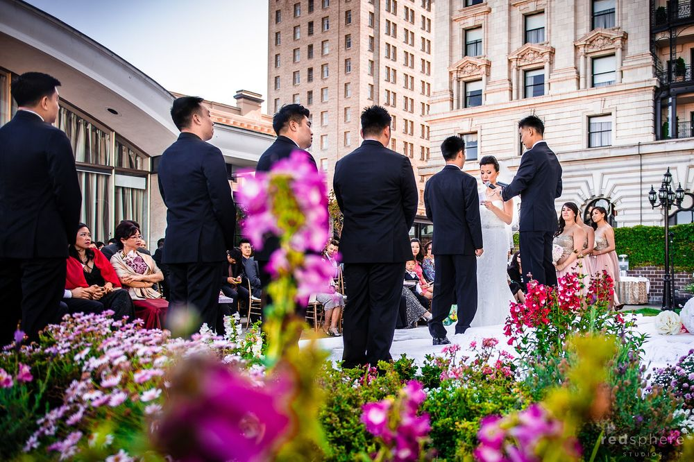Bride, Groom, Bridemaids', and Groomsmen Behind Fairmont Hotel's Flowers