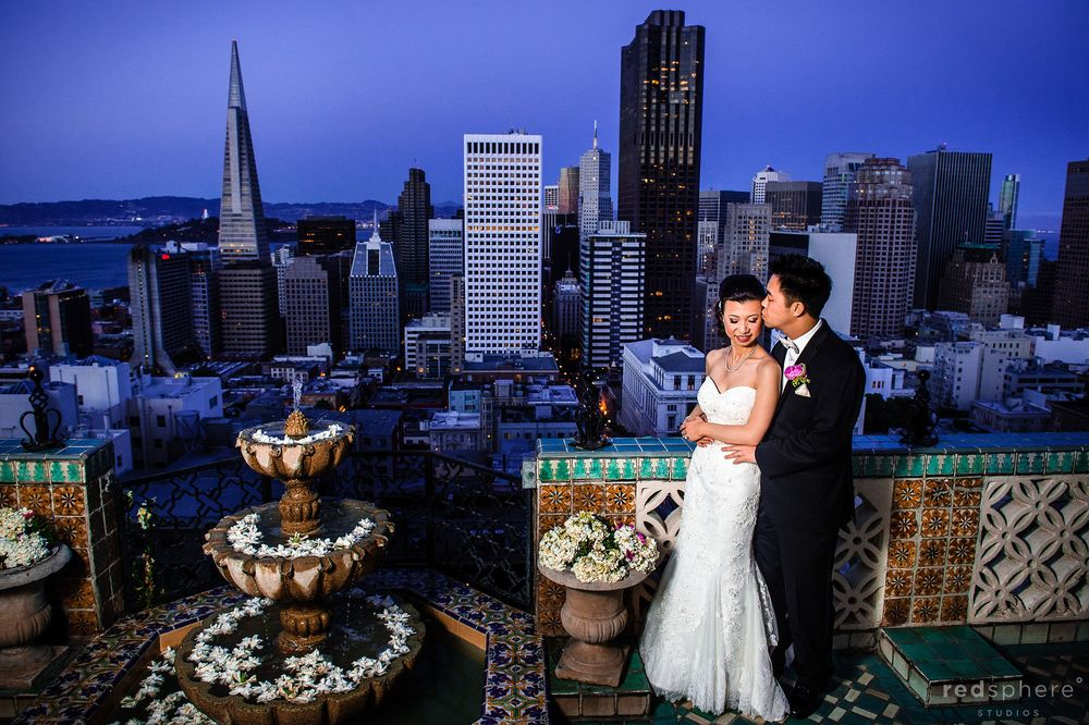 Groom Kisses Bride Against the San Francisco Skyline From Fairmont Hotel Balcony