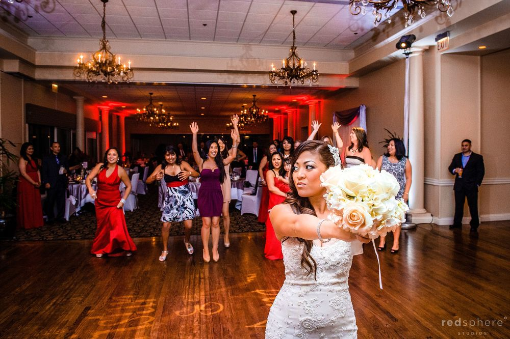 Bride Holding Out Her Bouquet of Flowers On The Dance Floor