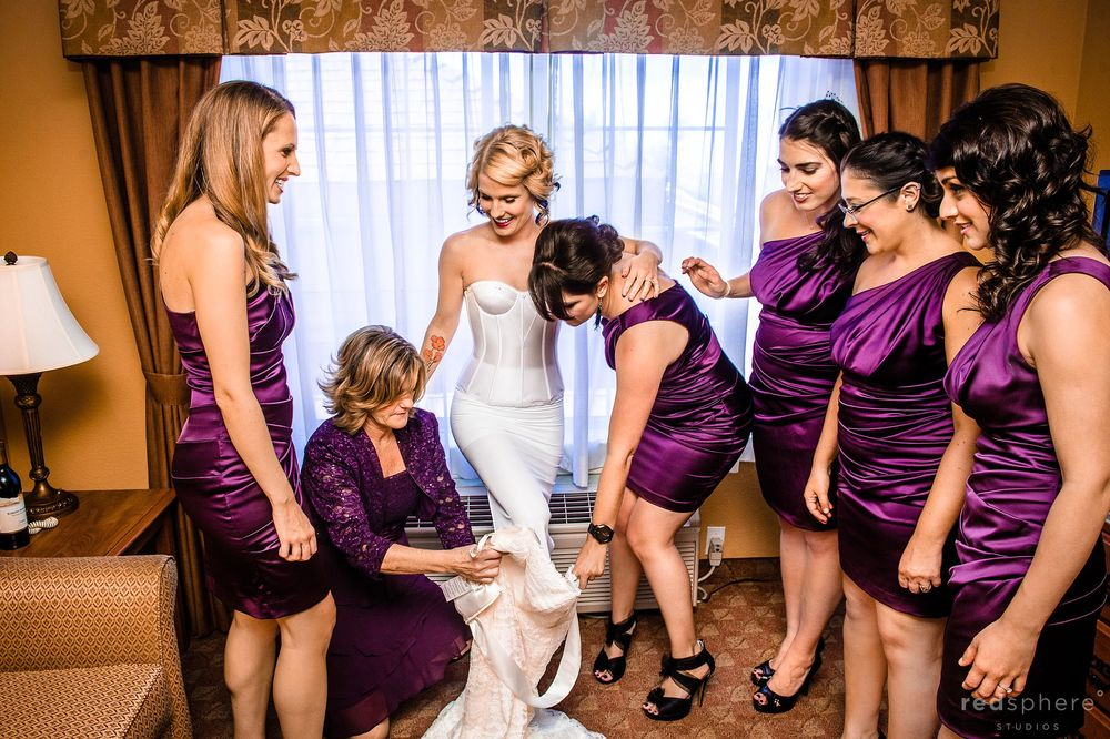 Bridesmaids' Help Bride Into White Wedding Dress