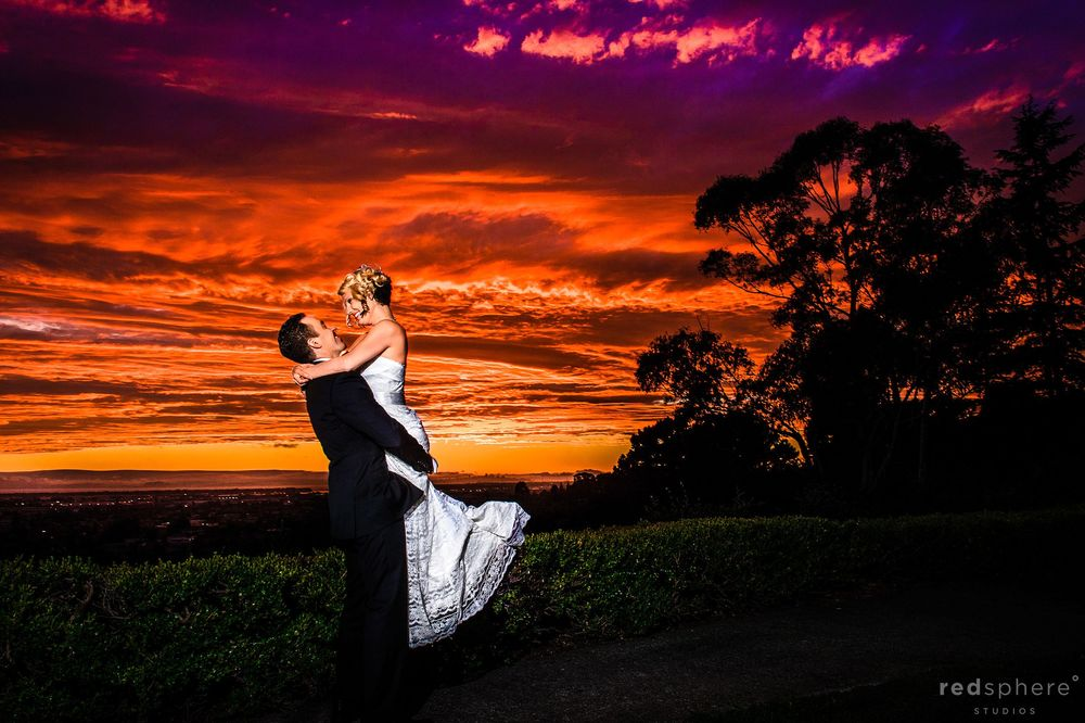 Groom Carries Bride, Tree Silhouette With Burning Orange Sunset