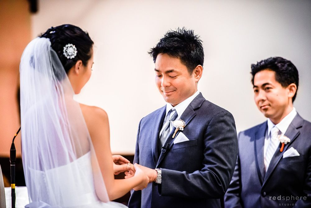 Bride Places Ring Onto Grooms Finger, Half Moon Bay Wedding