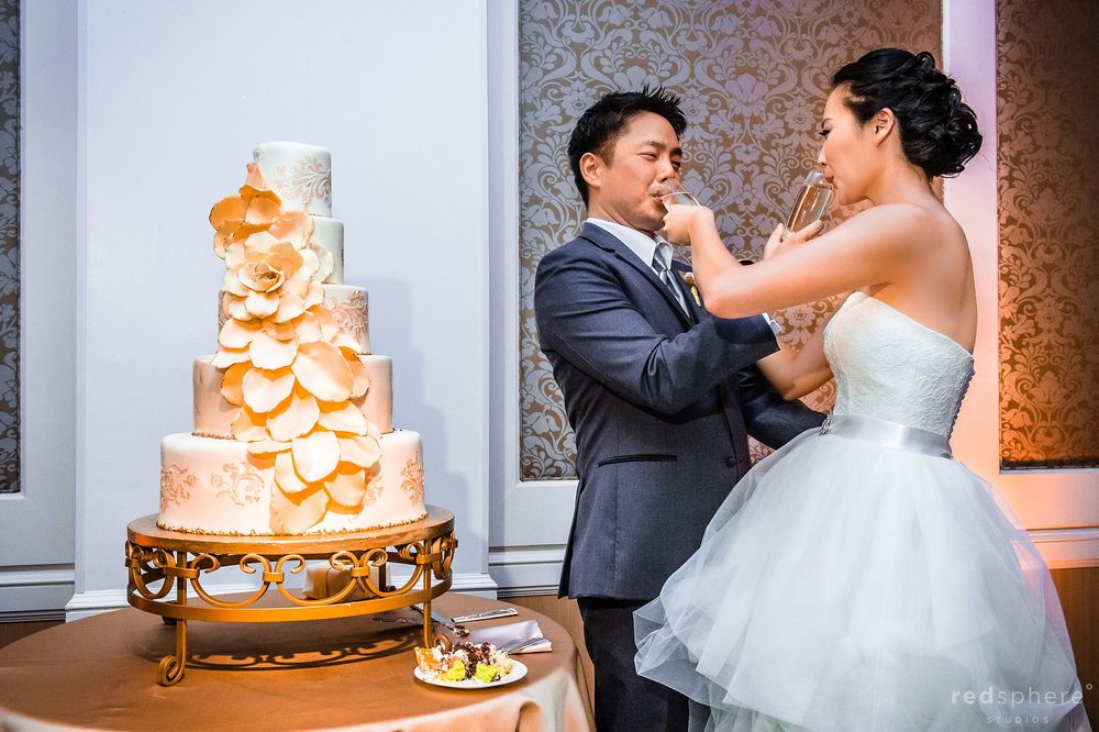 Newly Wed Couple Having Fun With Champagne and Wedding Cake
