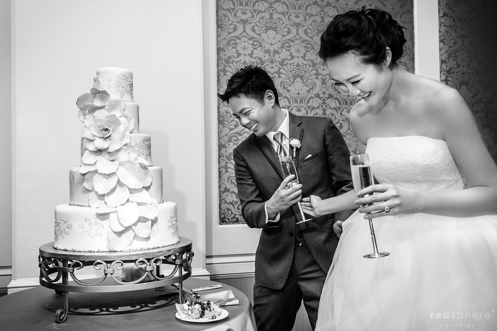 Groom Peeks at Wedding Cake, Black and White