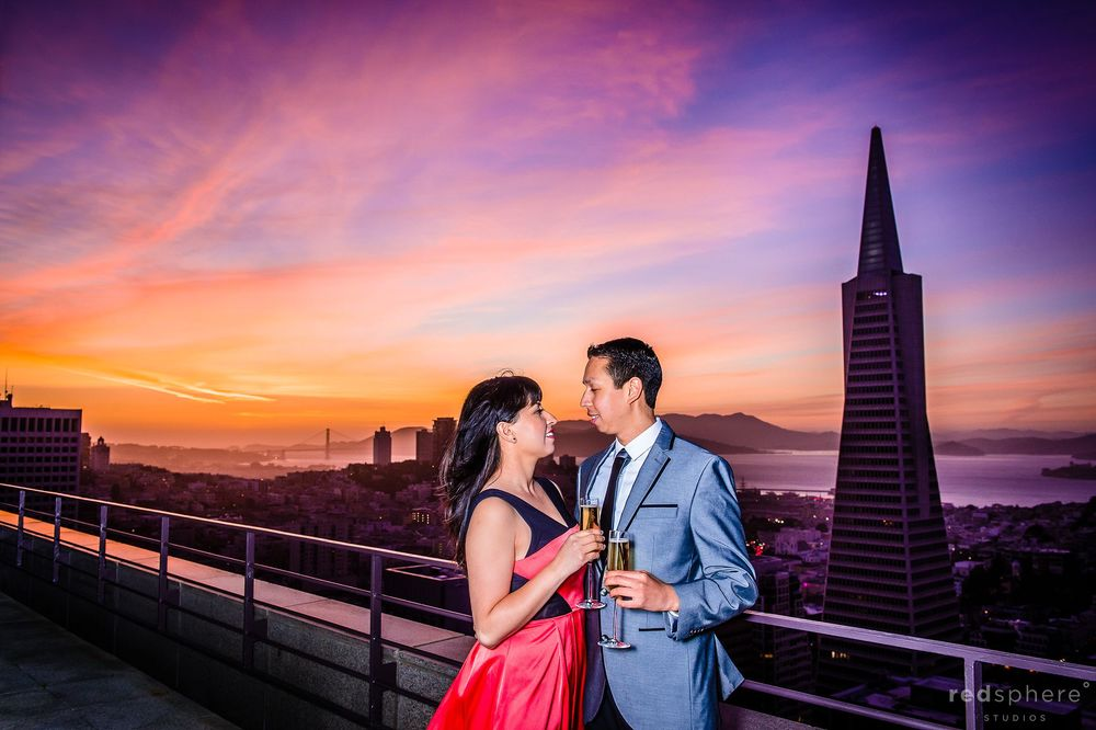 Couple Holding Champagne on the Balcony of Loew's Regency Hotel, San Francisco Vibrant Sunset Engagement
